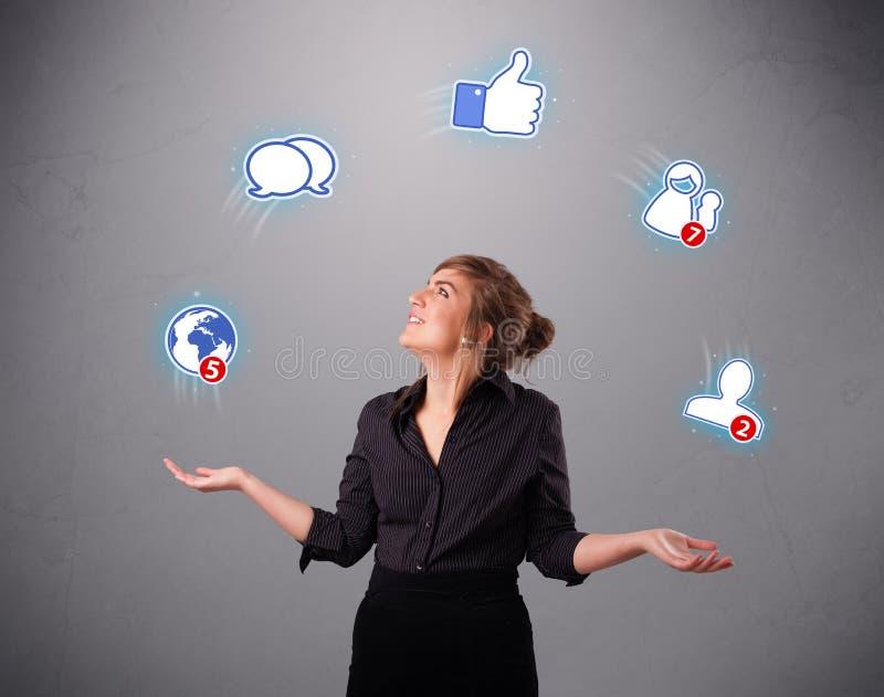 Mujer que hace juegos malabares con los iconos sociales de la red imágenes de archivo libres de regalías