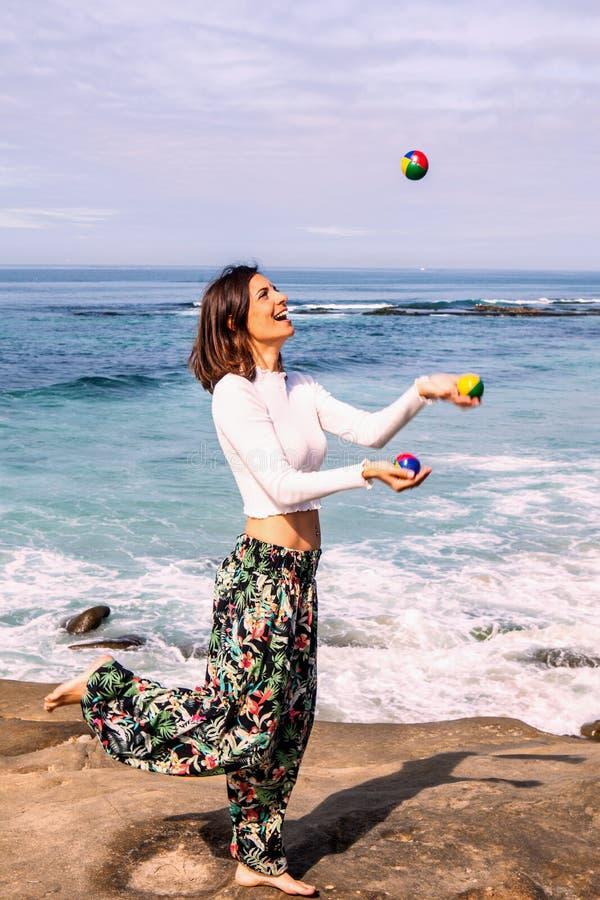 Mujer que hace juegos malabares por el océano fotografía de archivo