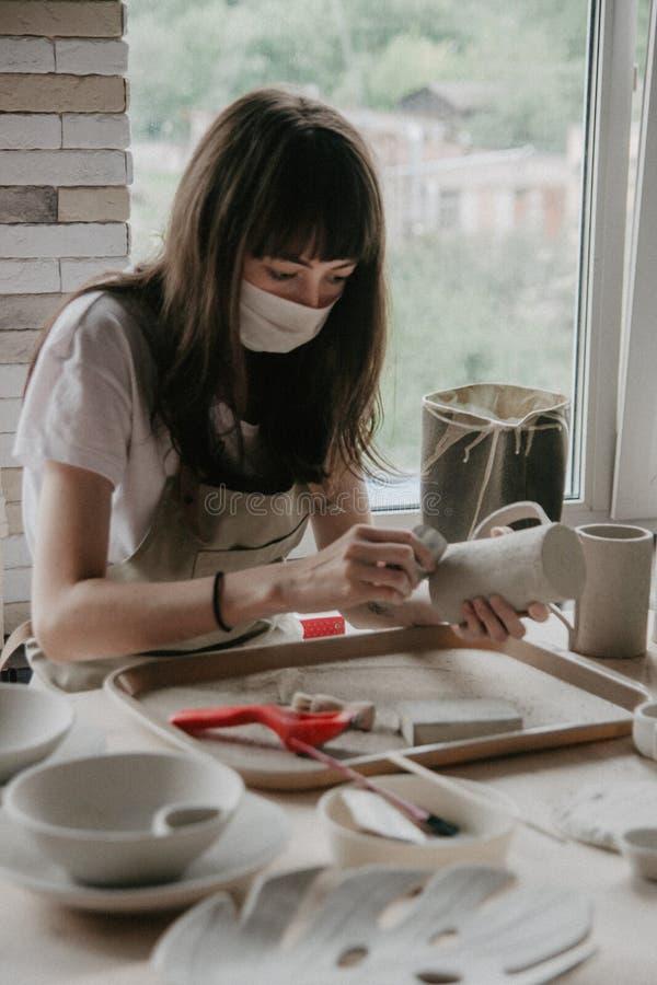 Mujer que hace la cerámica Primer del proceso de enarenar la placa de la arcilla fotografía de archivo