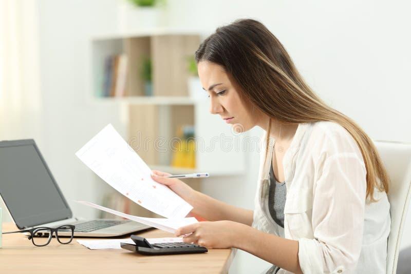 Mujer que hace la contabilidad que compara documentos imagenes de archivo