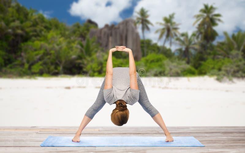 Mujer que hace la curva delantera ancho-legged de la yoga en la playa fotografía de archivo libre de regalías