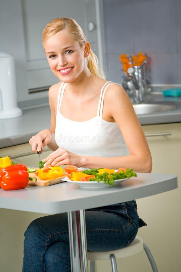 Mujer que hace la ensalada en la cocina imagen de archivo libre de regalías