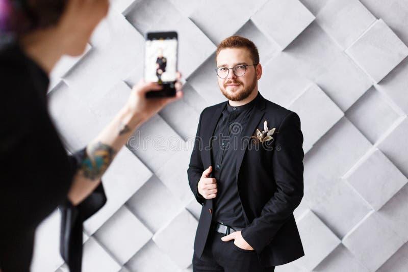 Mujer que hace la foto de novio en el teléfono en el fondo gris del estudio aislado imagen de archivo libre de regalías