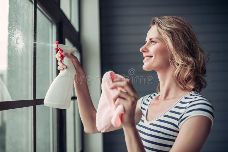 Mujer que hace la limpieza en casa imagenes de archivo