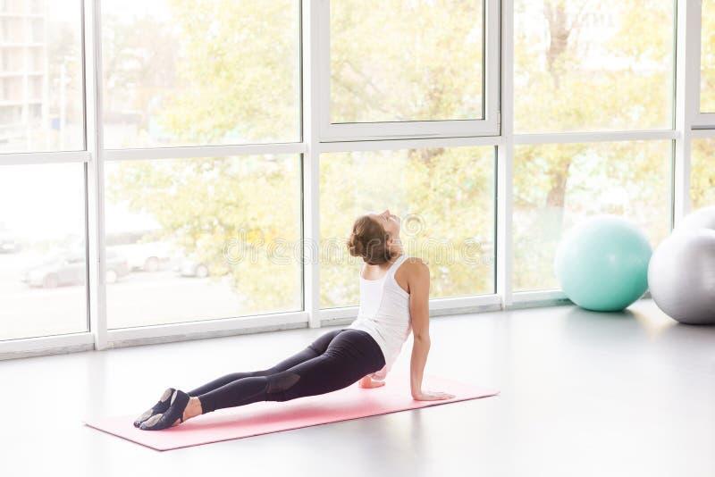 Mujer que hace la yoga, actitud de la cobra, postura de sana del  del gÄ del ¹ de Bhujaá… imagen de archivo