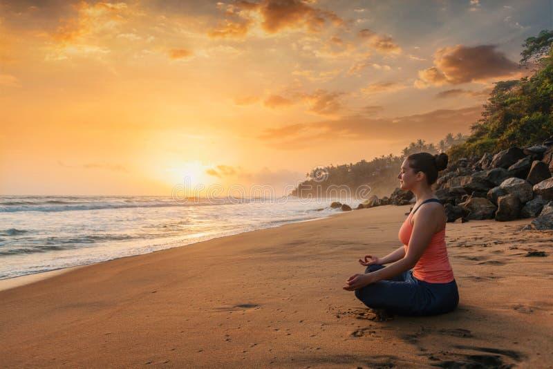 Mujer que hace la yoga en la playa - actitud del loto de Padmasana imagen de archivo