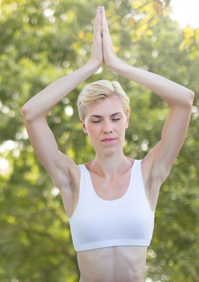 Mujer que hace la yoga que medita por los árboles imagen de archivo