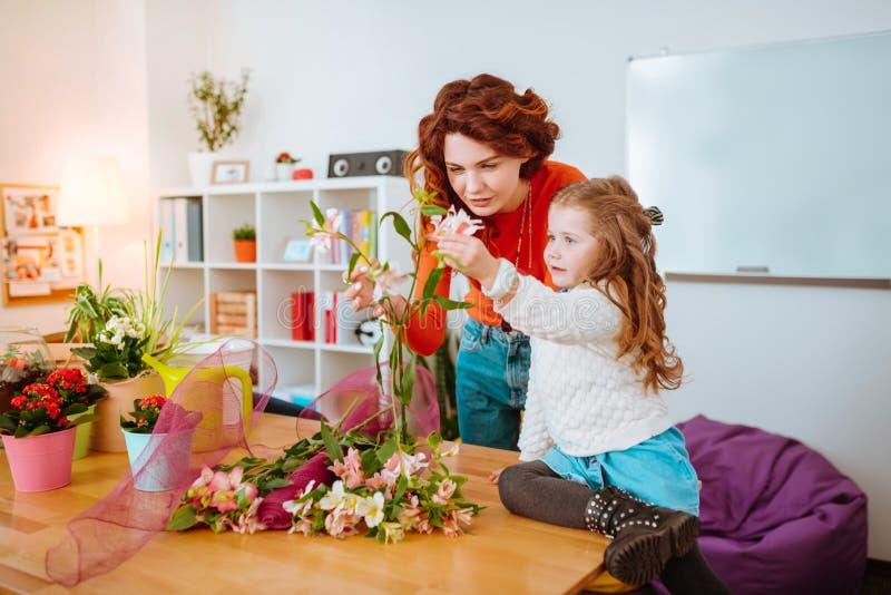 Mujer que hace las composiciones florales que miran las flores con la hija imagen de archivo