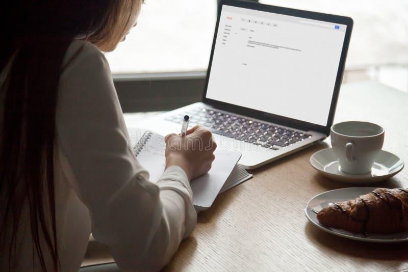 Mujer que hace las notas que leen la letra del correo electrónico en el ordenador portátil en café foto de archivo