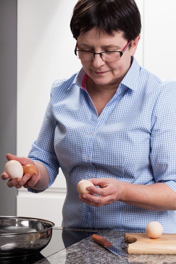 Mujer que hace los huevos revueltos fotos de archivo libres de regalías