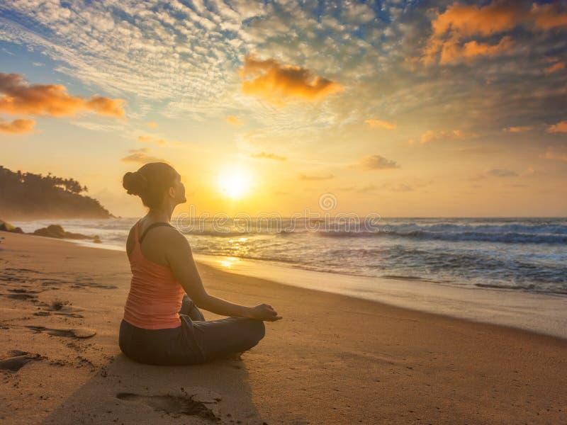 Mujer que hace los oudoors en la playa - actitud de la yoga del loto de Padmasana foto de archivo