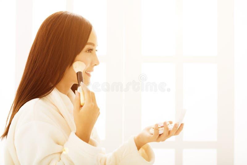 mujer que hace maquillaje delante del espejo del cuarto de baño fotos de archivo
