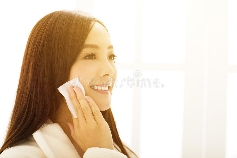 mujer que hace maquillaje delante del espejo del cuarto de baño imagen de archivo
