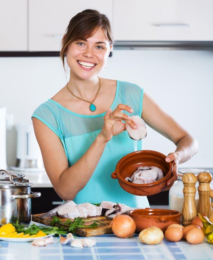 Mujer que hace pescado frito con patatas fritas foto de archivo