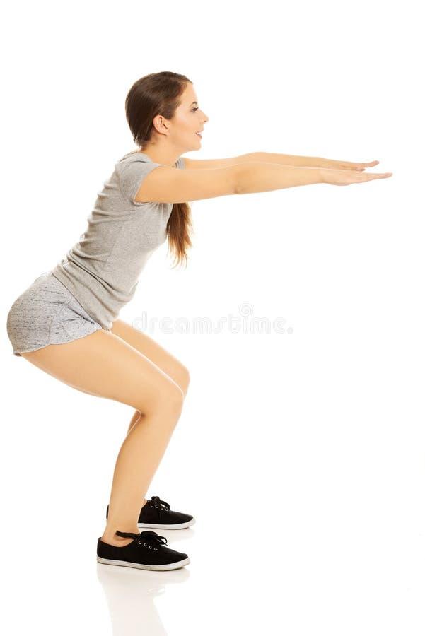 Mujer que hace posiciones en cuclillas imagen de archivo libre de regalías