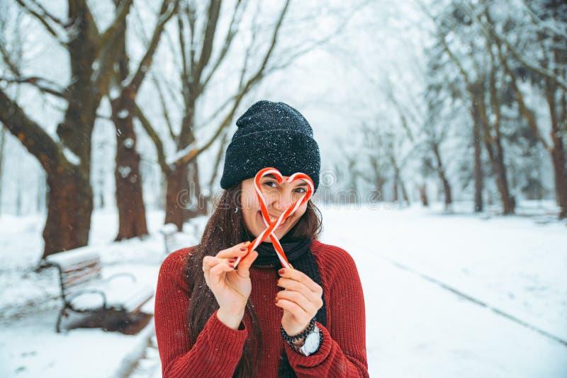 Mujer que hace símbolo del corazón con el caramelo de la Navidad afuera en parque nevado invierno imagen de archivo
