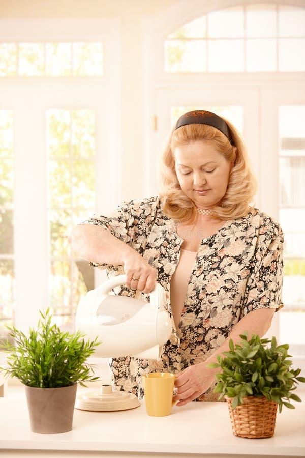 Mujer que hace té en cocina fotografía de archivo