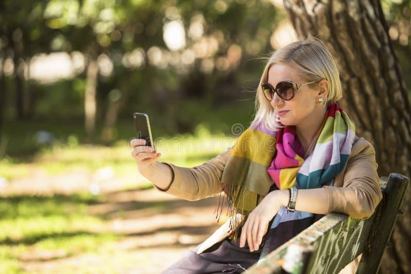 Mujer que hace un autorretrato con el smartphone que se sienta en banco en el parque foto de archivo libre de regalías