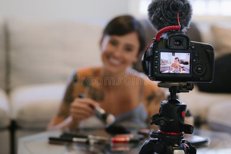 Mujer que hace un blog video en los cosméticos foto de archivo