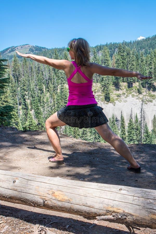 Mujer que hace una mediación de la actitud de la yoga con los brazos para arriba cerca del bosque i imagen de archivo