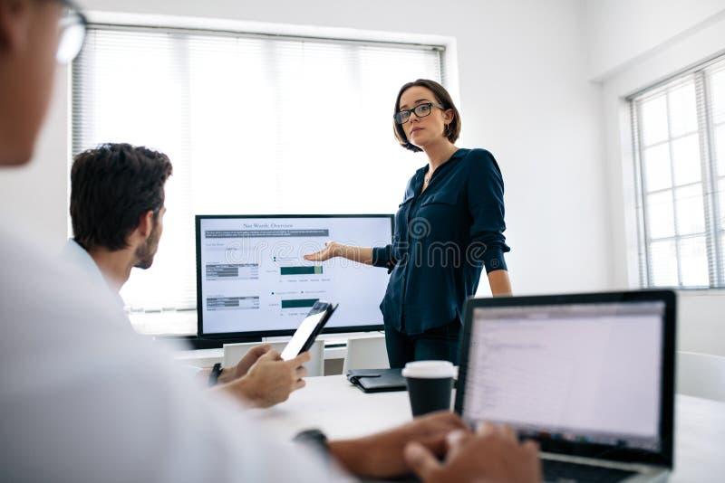 Mujer que hace una presentación en el trabajo imagen de archivo
