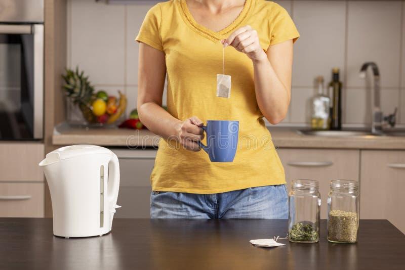 Mujer que hace una taza de té fotografía de archivo libre de regalías