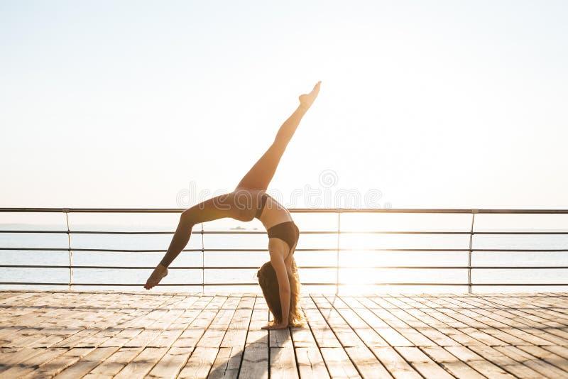 Mujer que hace yoga al aire libre por la mañana imagen de archivo