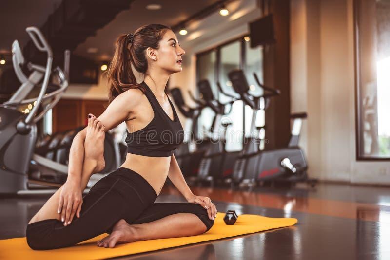 Mujer que hace yoga de doblez de las piernas en los entrenamientos de la aptitud que entrenan al fondo del centro del gimnasio Mu fotografía de archivo