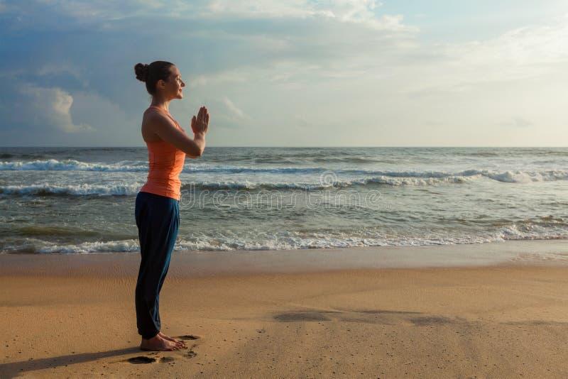 Mujer que hace yoga en la playa fotos de archivo libres de regalías