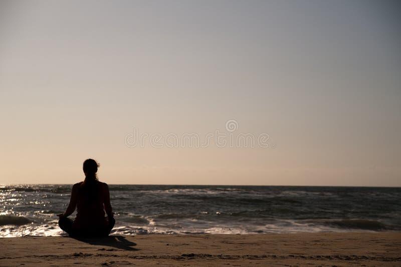 Mujer que hace yoga en la playa. imagen de archivo libre de regalías