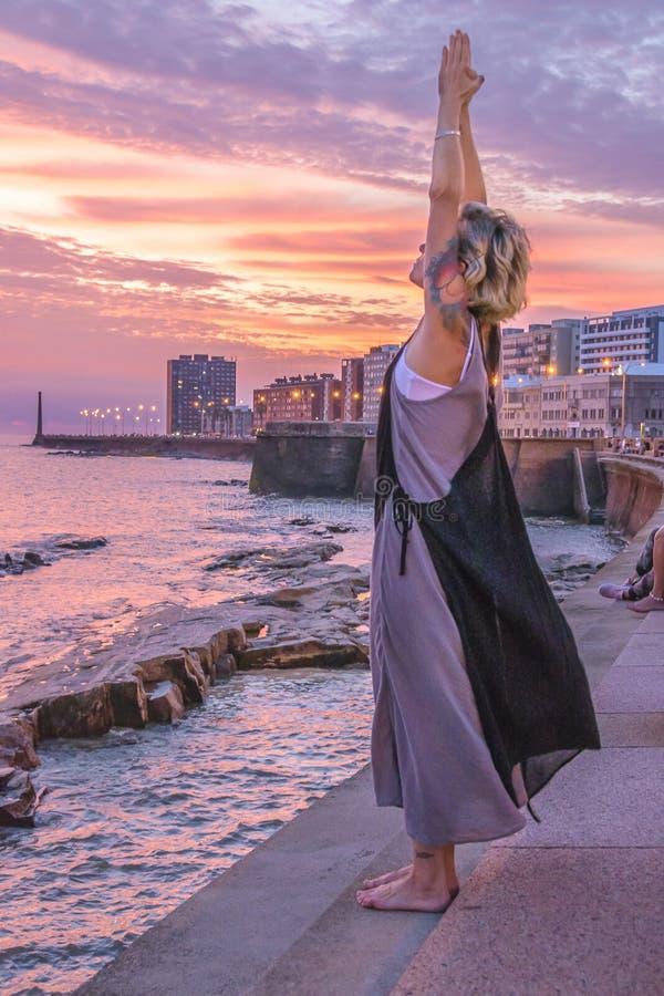 Mujer que hace yoga en Rambla Sur, escena de la puesta del sol de Montevideo imagenes de archivo