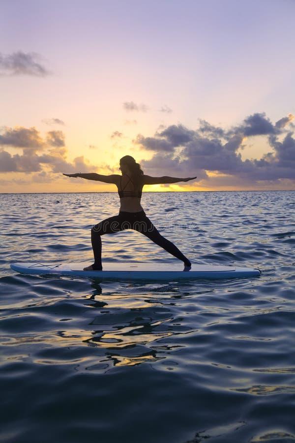Mujer que hace yoga en un tablero de paleta fotografía de archivo libre de regalías