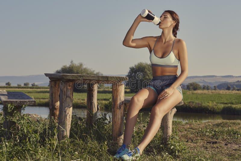 Mujer que hidrata después de funcionamiento imágenes de archivo libres de regalías