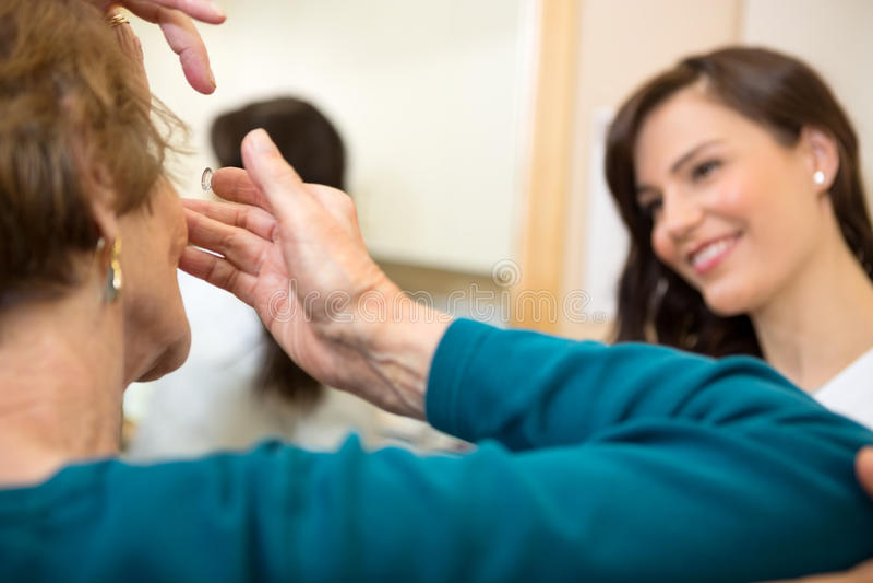 Mujer que inserta la lente de contacto fotos de archivo libres de regalías
