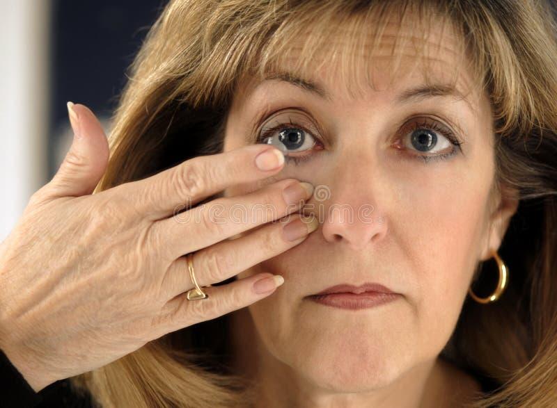 Mujer que inserta la lente de contacto en ojo imagen de archivo