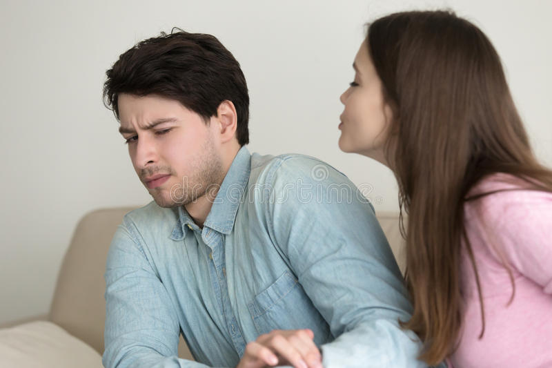 Mujer que intenta besar al hombre, él que da vuelta lejos, rechazándola imagen de archivo