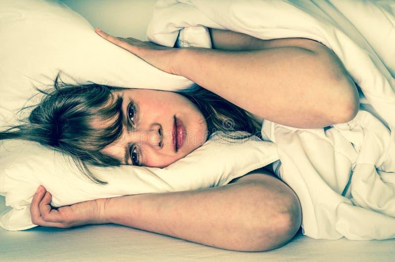 Mujer que intenta dormir, ella oídos de la cubierta con la almohada fotos de archivo libres de regalías