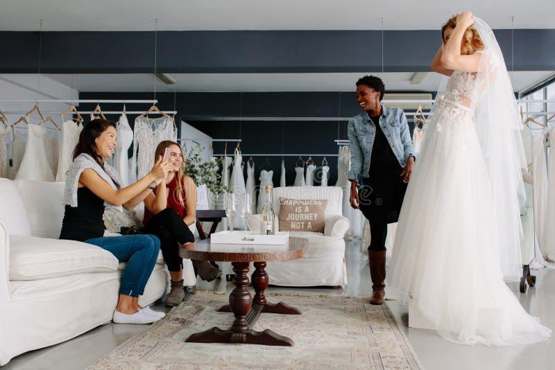 Mujer que intenta en el vestido de boda en una tienda con los amigos imágenes de archivo libres de regalías