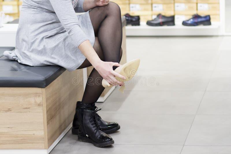 Mujer que intenta en los nuevos zapatos en zapatería Compre nuevos zapatos en boutiq foto de archivo libre de regalías
