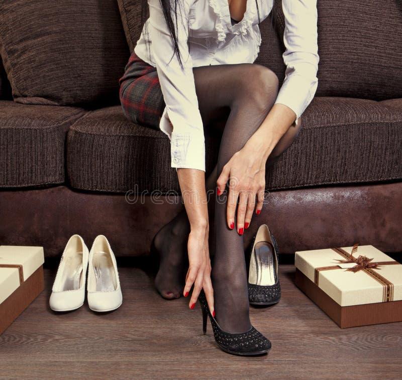 Mujer que intenta en varios pares de zapatos imagenes de archivo