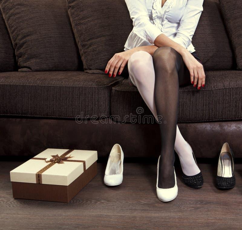 Mujer que intenta en varios zapatos fotos de archivo