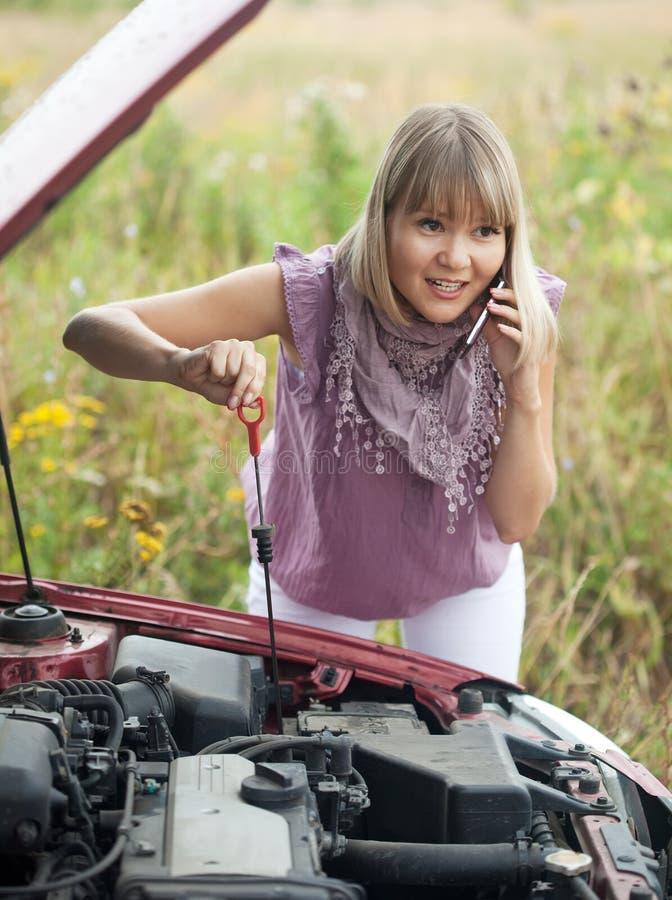 Mujer que intenta fijar el coche imagenes de archivo