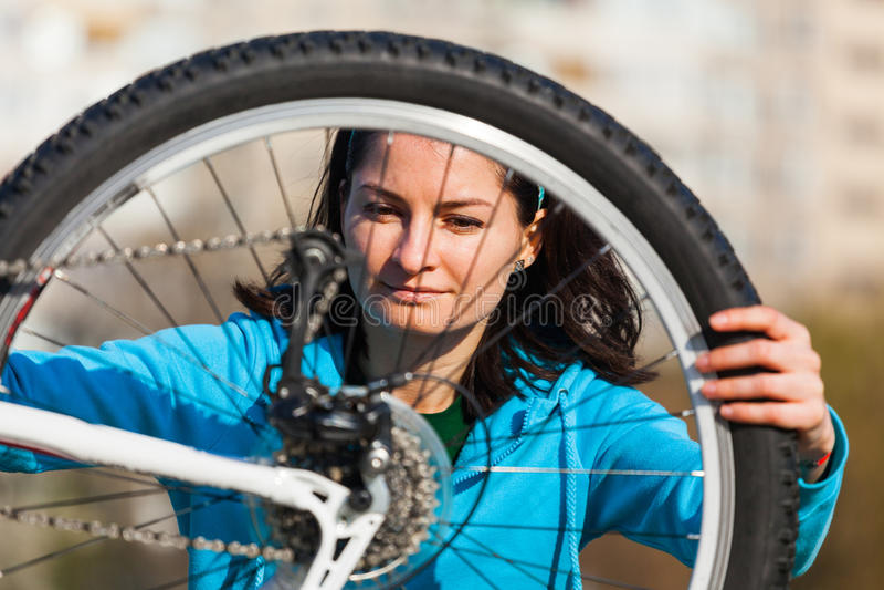 Mujer que intenta fijar la bici fotografía de archivo