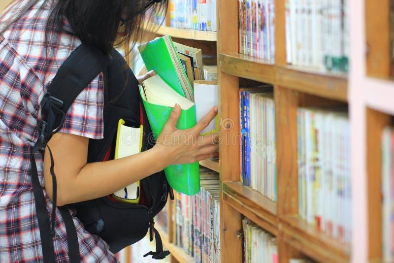 Mujer que intenta robar los libros en el estante en el cuarto de la biblioteca, robo patológico, cleptomanía fotos de archivo