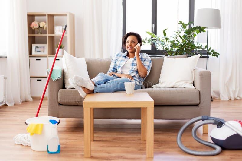 Mujer que invita a smartphone despu?s de la limpieza casera imagen de archivo libre de regalías