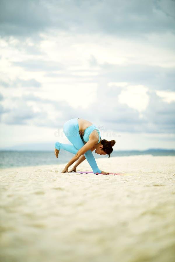 Mujer que juega actitud de la yoga en la playa de la arena fotos de archivo