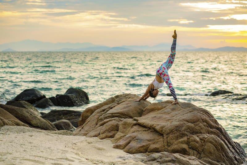Mujer que juega actitud de la yoga en la playa del mar contra risin hermoso del sol foto de archivo