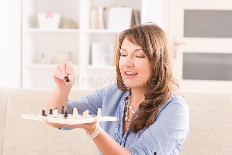 Mujer que juega a ajedrez en casa imagen de archivo libre de regalías