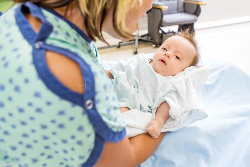 Mujer que juega con Babygirl lindo en hospital foto de archivo libre de regalías