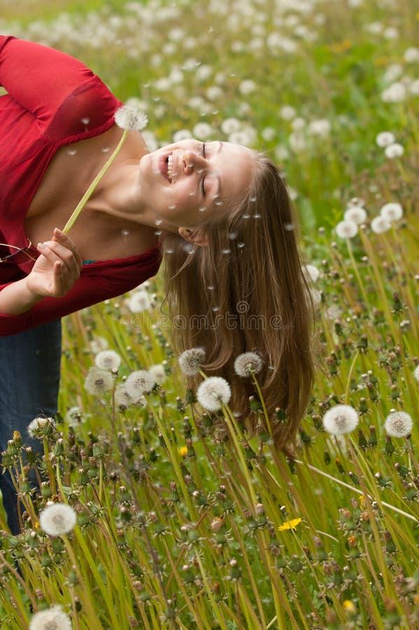 Mujer que juega con el diente de león fotografía de archivo libre de regalías